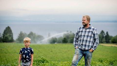 Per Odd Gjestvang og sønnen Håkon i en potetåker med et av vanningsanleggene i bakgrunnen. Grønnsaksbonden har delvis berget unna årets avlinger ved å pumpe opp vann fra Mjøsa.