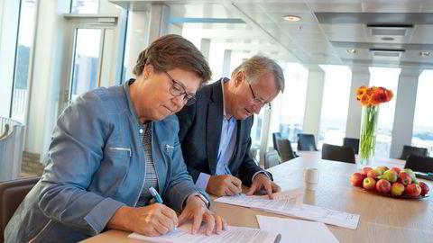 Banktoppene Turid Grotmoll i Sparebanken 1 (til venstre) og Rune Bjerke i DNB signerer avtalen om forsikringsfusjonen som ble varslet i juni.