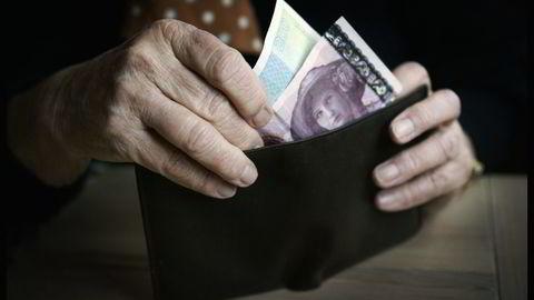 En eldre dame har tatt ut ut penger fra minibanken og står med lommeboken med penger i hendene. Foto: Tor Richardsen / Scanpix.