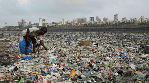 En mann samler inn plast og andre resirkulerbare materialer fra stranda langs Arabiahavet i Mumbai i India.