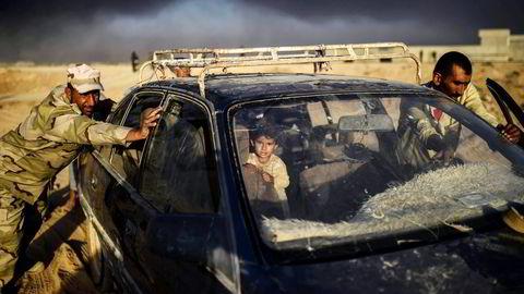 Det antas at om lag én million sivile fortsatt bor i Mosul. Hjelpeorganisasjonene frykter en humanitær katastrofe. Her hjelper soldater sivile med å nå frem til en flyktningleir i byen Qayyarah sør for Mosul. Foto: Bulent Kilic/Afp/NTB Scanpix