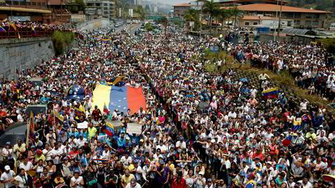 Venezuela innfører en rekke tiltak som følge av alle strømbruddene. På bildet hører tilhengerne av opposisjonsleder og selvutnevnt president Juan Guaidó ham tale lørdag i San Antonio.
