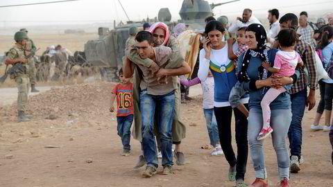 Syriske kurdere strømmer over grensen til Tyrkia som følge av at IS har tatt kontroll over flere titalls landsbyer i Nord-Syria. Foto: Reuters / NTB scanpix