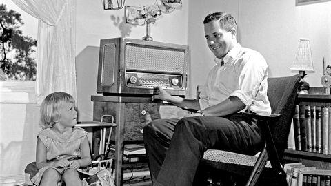 August 1959. Skuespiller og imitator Rolf Just Nilsen lytter på «Ønskekonserten» på radio i sin stue, sammen med lille Brita. Foto: Aage Storløkken/NTBScanpix
