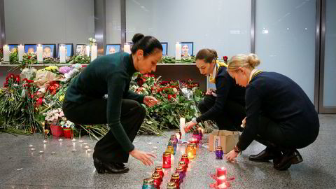 Kolleger av crewet på Ukraine International Airlines tenner lys og legger ned blomster på flyplassen Borispil utenfor Kiev.