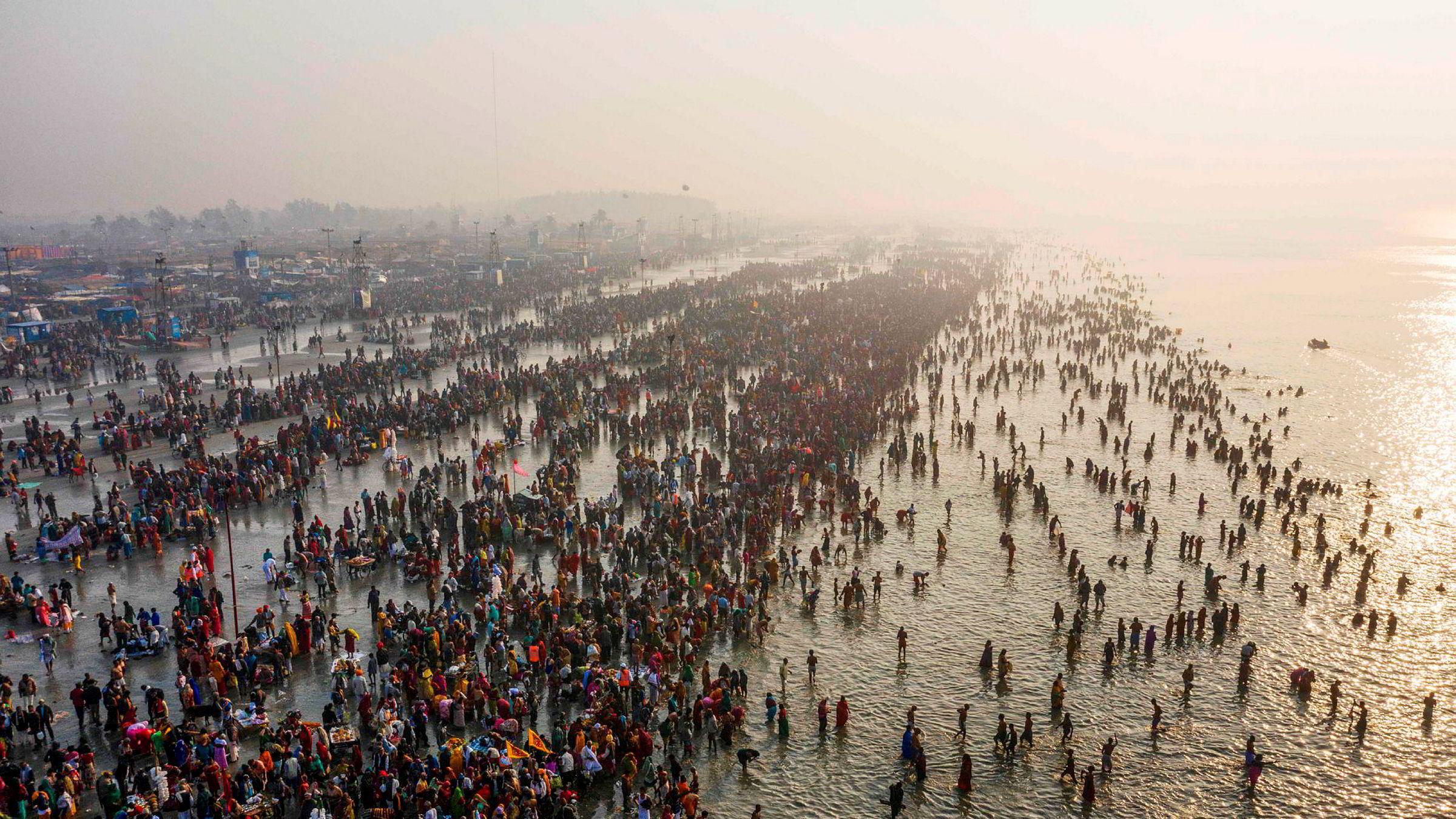 TOPSHOT – In this aerial photo taken on January 14, 2020, Hindu devoteks gather to take a holy dipp in the Bay of Bengal during the Gangasagar Mela, at Sagar Island, some 150 kilometers south of Kolkata. (Photo by XAVIER GALIANA / AFP) ---