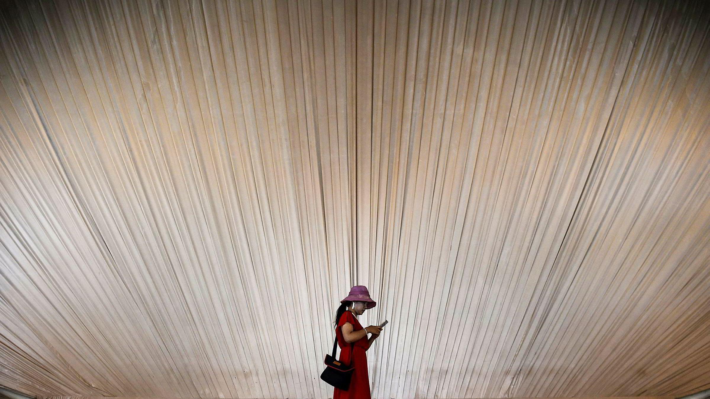 En kvinne ser på mobiltelefonen sin, mens hun vandrer rundt på et utstillingssenter i Shanghai, Kina. Smarttelefonsalget i første kvartal falt med hele 21 prosent sammenlignet med foregående kvartal.