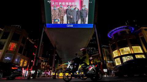 En videoskjerm i Beijing viser en nyhetssending hvor Kinas president Xi Jinping besøker Wuhan den 19. mars. Observatører mener nødhjelpsinnsatsen fra Kina under koronakrisen indirekte har hjulpet Kinas president Xi Jinping å forbedre landets image internasjonalt.
