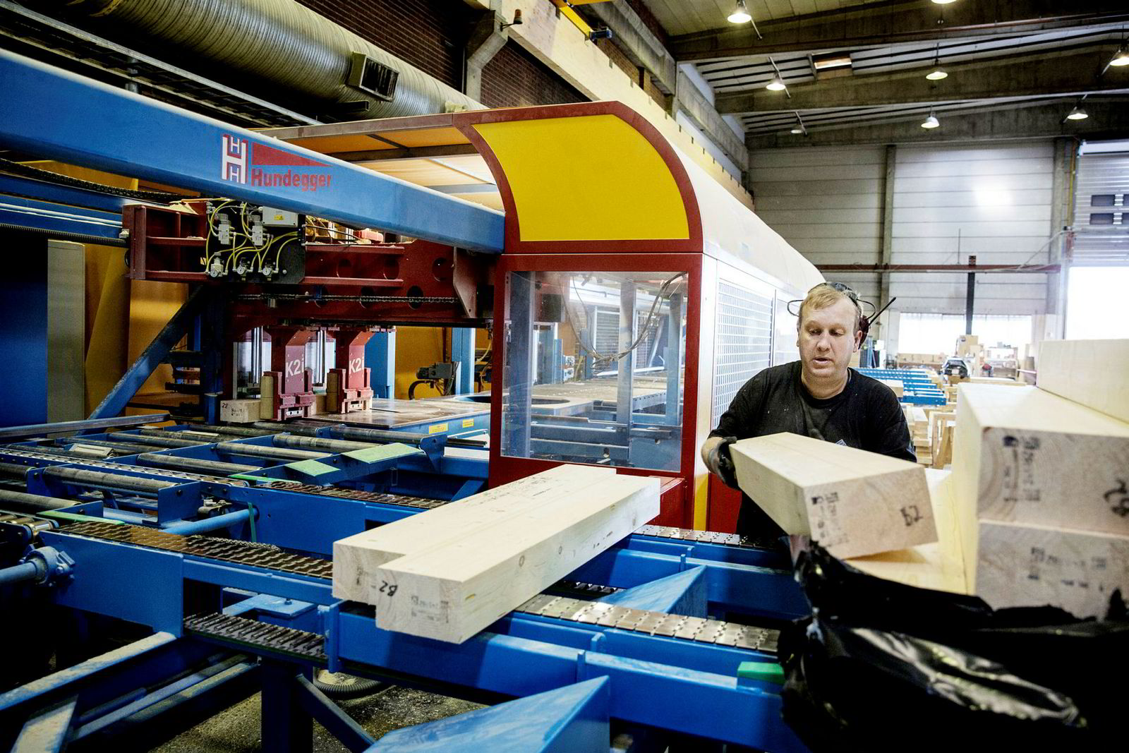 Fagarbeider Marius Skogstad står ved en maskinen som har erstattet rundt åtte personer.