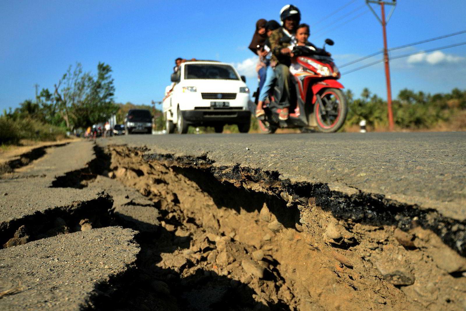 En bil passerer en revne i en vei i Kayangan-distriktet, tre dager etter et jordskjelv rammet området. Rundt 160.000 mennesker ble hjemløse fra det dødelige skjelvet, og må ty til midlertidig ly, og mangler mat.
