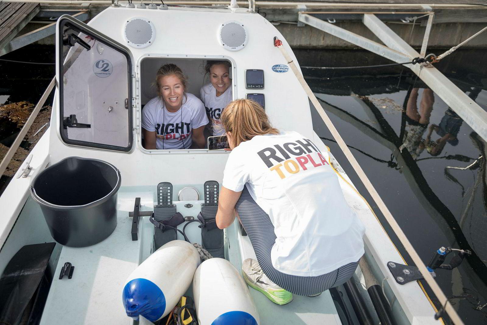 Sophie Stabell fotograferer Cornelia Bull, til venstre og Hege Svendsberget i akterkabinen på robåten de skal bruke over Atlanterhavet. Bildet skal brukes på hjemmesiden til jentene som kaller seg Rowegians. Bøtten til venstre er for øvrig båtens toalett.