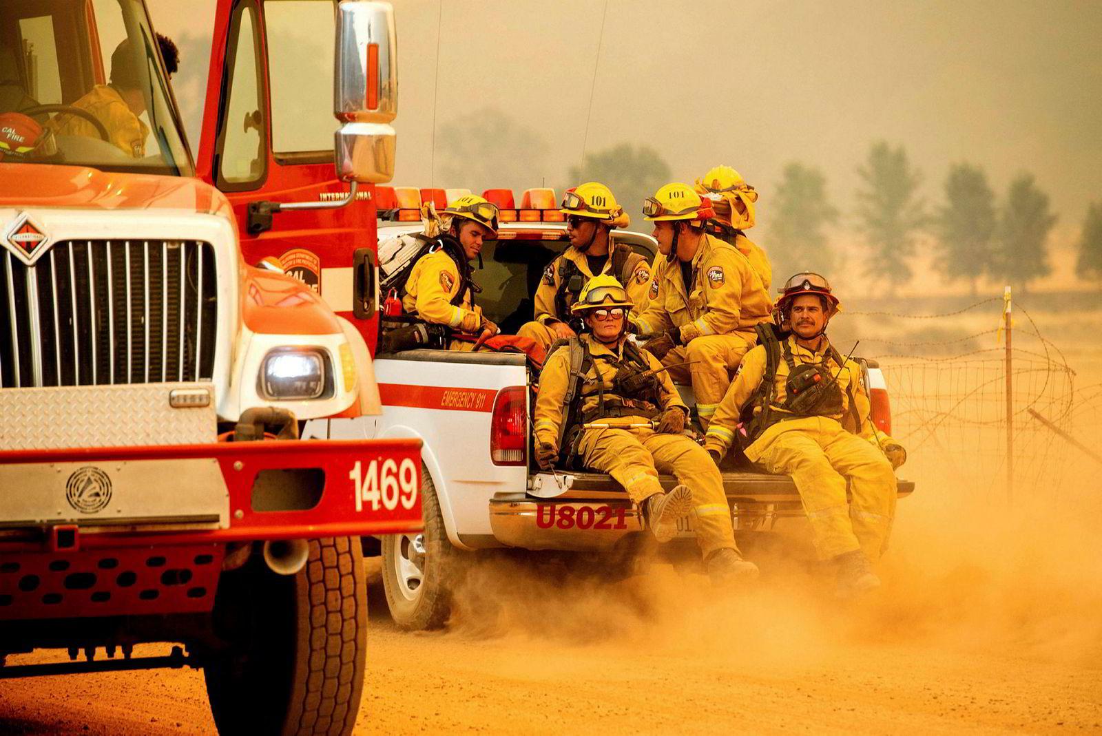 Et brannmannskap sitter bakpå en pickup mens de kjemper mot Ranch-brannen nær Clearlake Oaks.