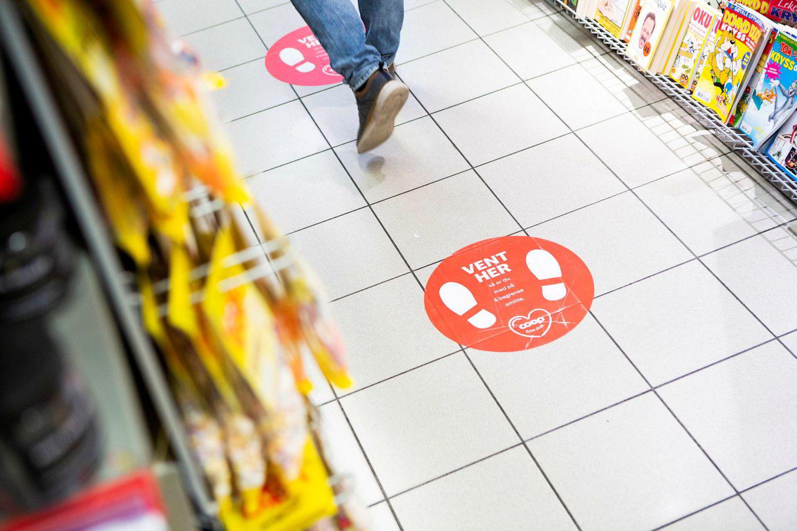 Klistremerker på gulvet gir kundene ved Coop Extra på Manglerudsenteret en påminnelse om viktigheten av å holde én meter avstand under pandemien. Etterspørselen etter denne typen klistremerker har økt betraktelig som følge av koronaviruset.