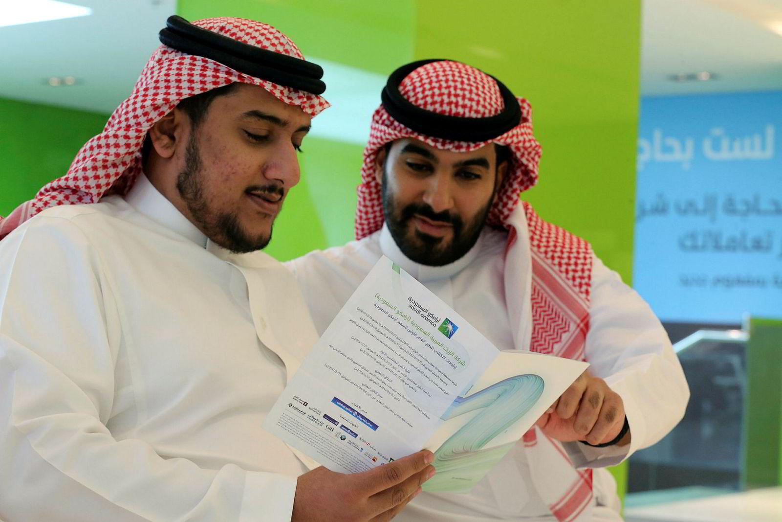 Saudiarabiske menn leser gjennom prospektet som ble sluppet før børsnoteringen av Saudi Aramco.