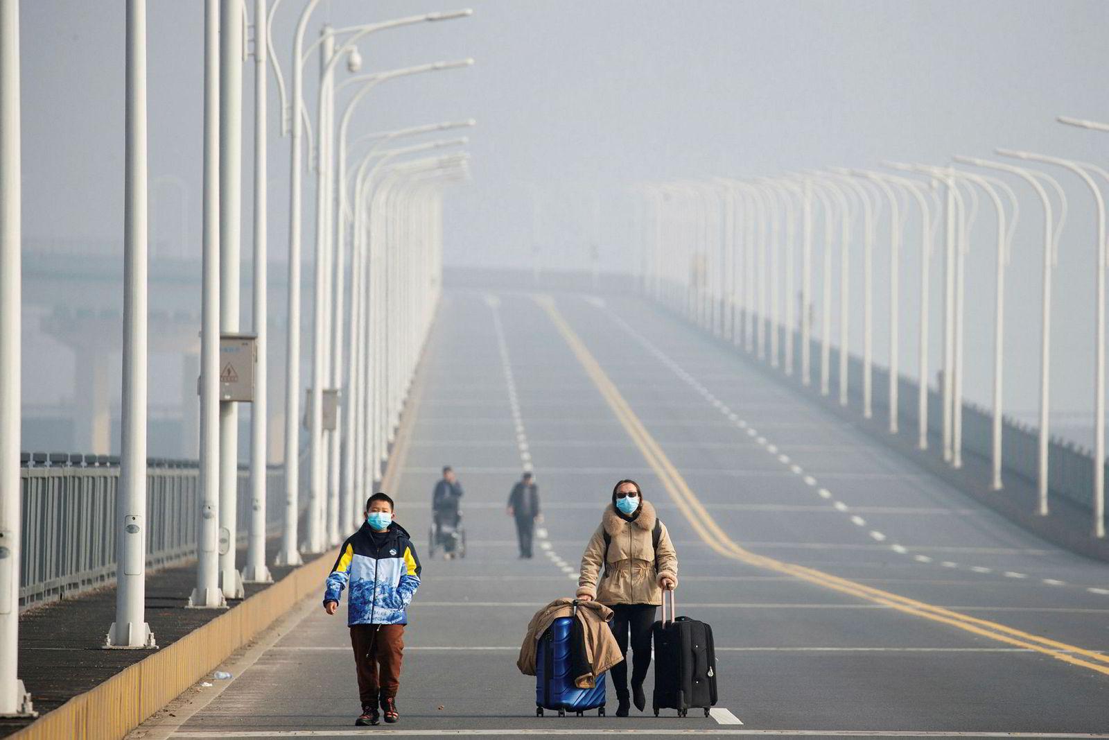 Mor og sønn evakuerer fra Wuhan og Hubei-provinsen over Jinjiang-broen som krysser Yangtze-elven.