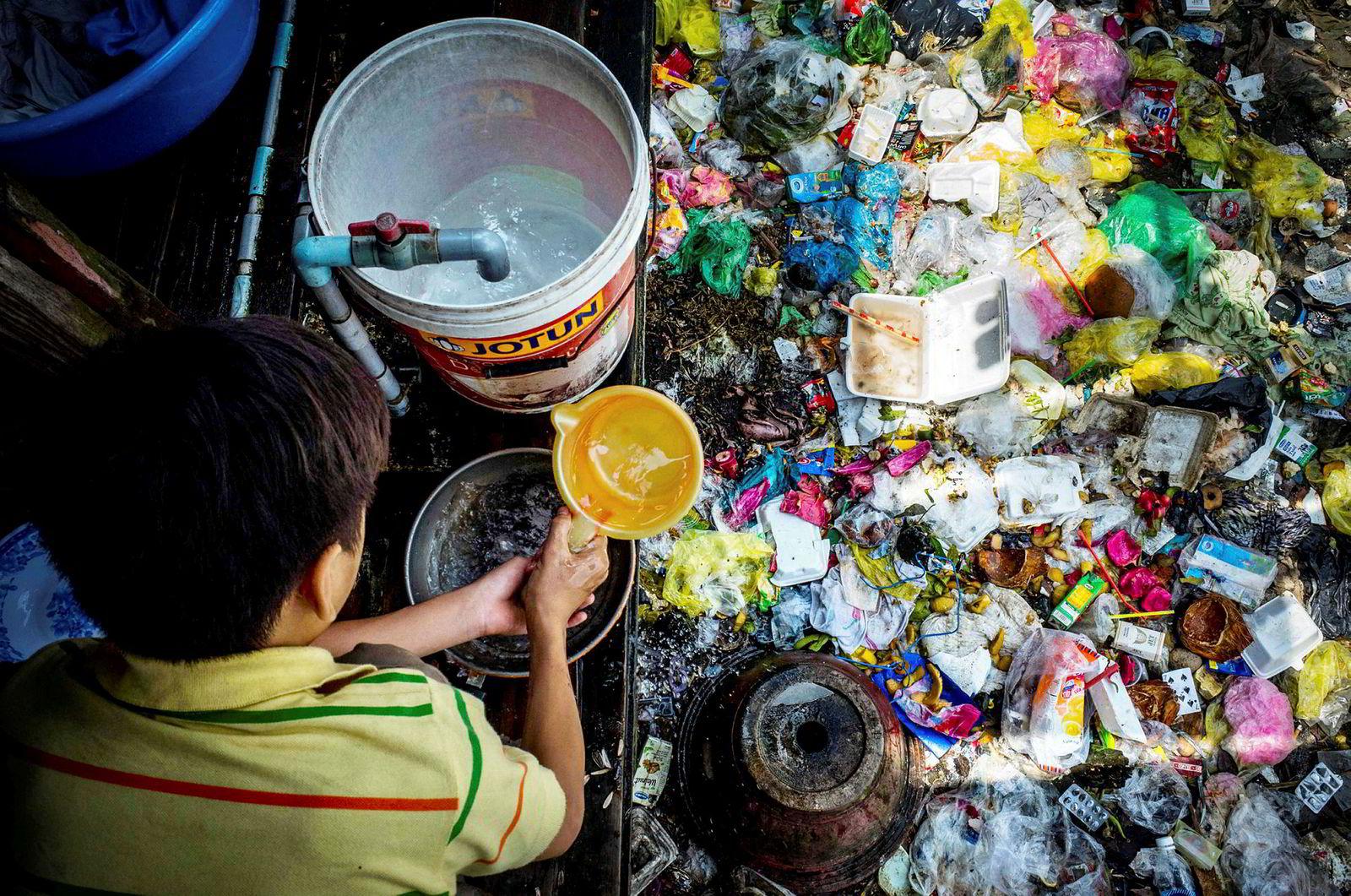 En gutt tar oppvasken ved elvebredden o Xuyen Tam-kanalen. Forurensing og søppel er et stort problem i elveområdene i Ho Chi Minh.