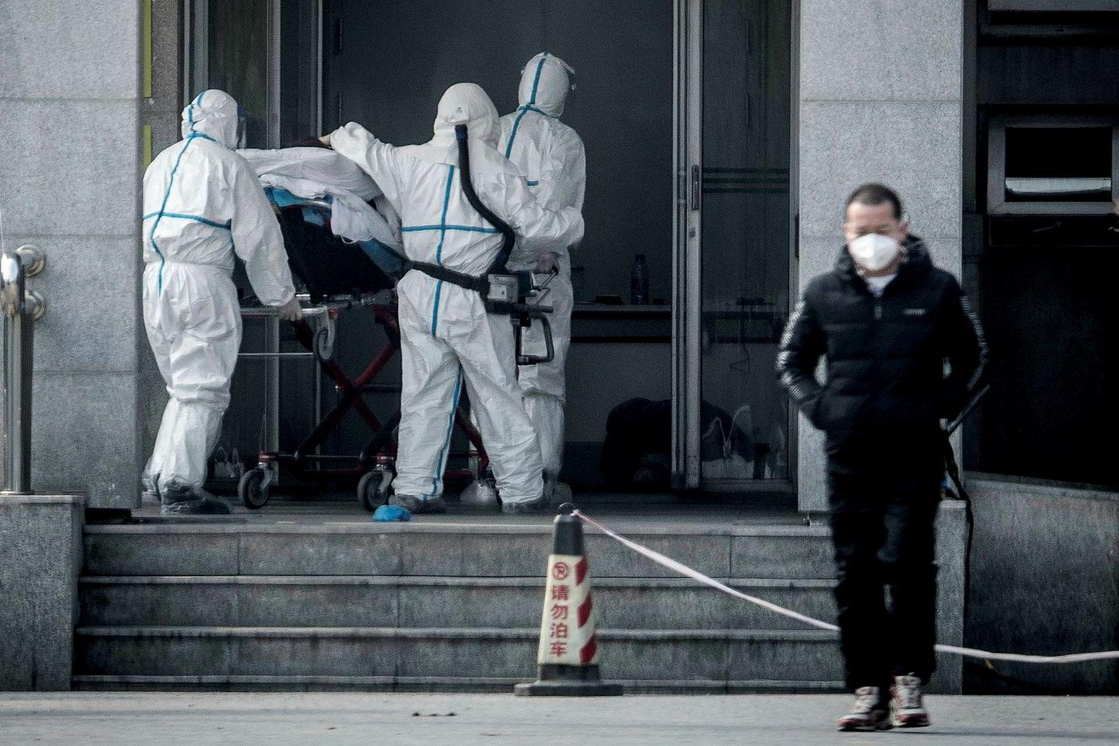 Et nytt virus som kan føre til alvorlig lungesykdom, smitter mellom mennesker, bekrefter kinesiske myndigheter. I løpet av 48 timer er antall bekreftede smittede tredoblet til over 220. Her fraktes en pasient inn til Jinyintan-sykehuset i Wuhan i Kina.
