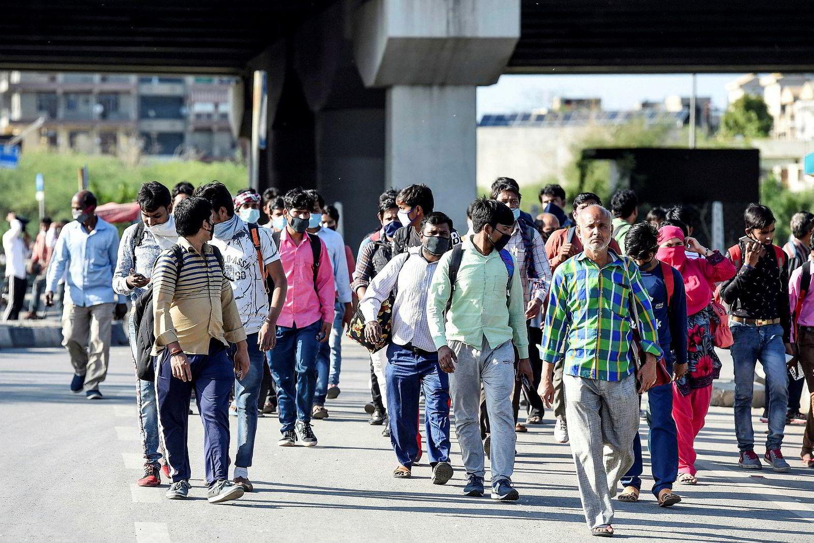 Tusener av mennesker, både unge menn og hele familier, tok bena fatt etter at myndighetene kunngjorde en 21 dager lang nedstengning for å bremse koronaviruset. Her fra New Delhi fredag. Millioner av mennesker, blant dem bygningsarbeidere, hushjelper, taxisjåfører og andre i uformell sektor, mistet med øyeblikkelig virkning all inntekt da indiske myndigheter denne uken stengte ned store deler av landet.