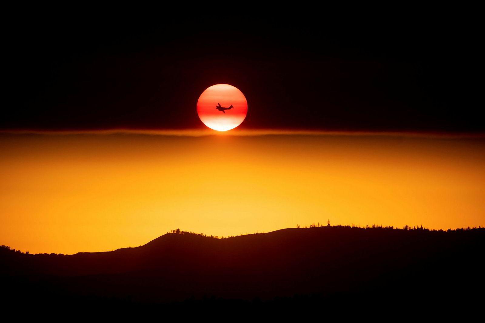 Et fly som kjemper mot Ferguson-brannen passerer solen på vei ned i Mariposa, nær nasjonalparken Yosemite.