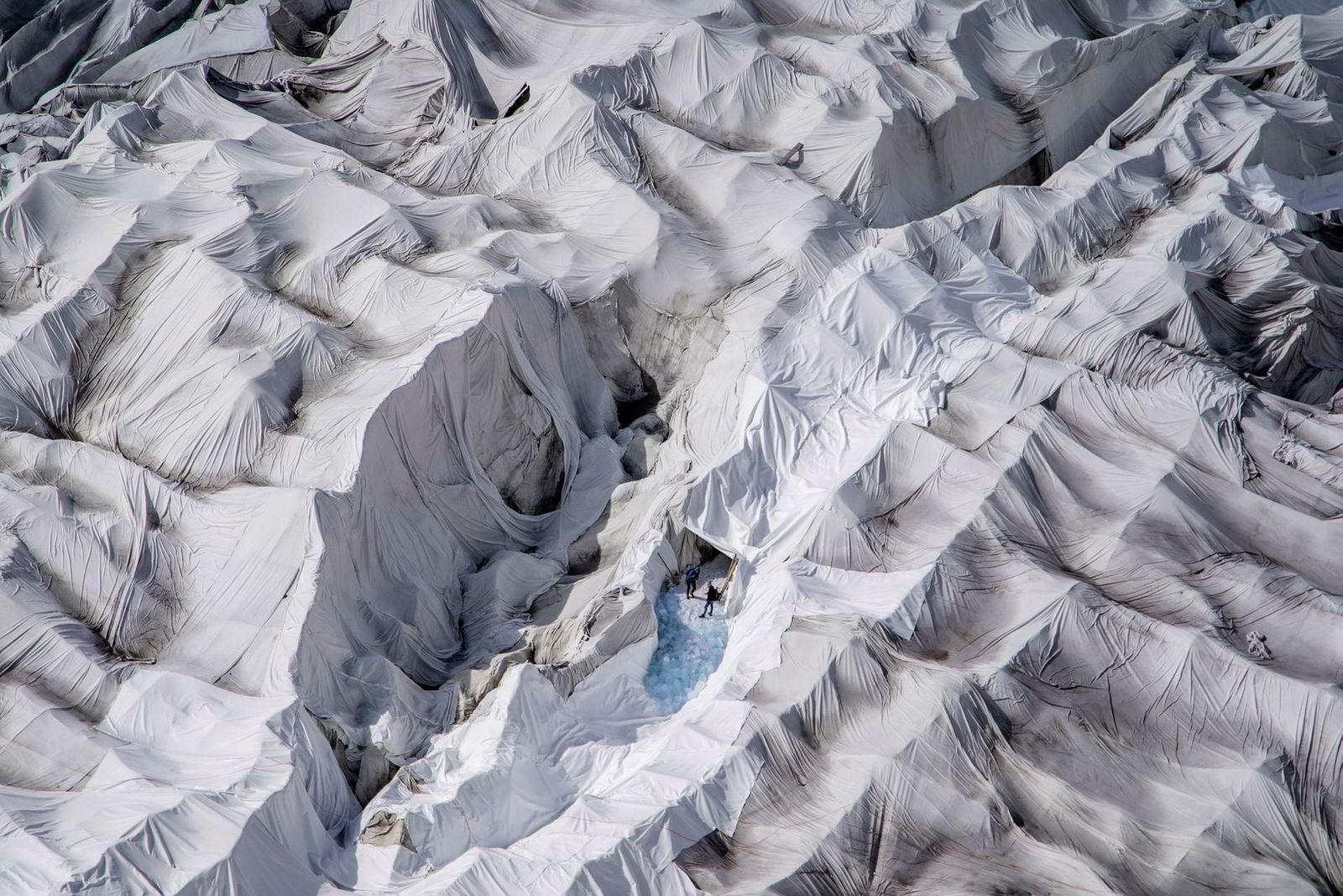Lakenskrekk: Flere hundre kvadratmeter av Rhonebreen i Sveits er dekket av hvite, enorme flislaken. Flisteppene er med på å bremse opp smeltingen av isgrotten, som er levebrødet til mannen bak flisteppene. Philipp Carlen er fjerde generasjons istunnelbygger på breen. I de senere år har han sett flere og flere turister komme for å se den døende isbreen før den forsvinner helt. Teppene han bruker er med på å kjøle ned breen og dempe effekten av solen, men han innser at det er en tapt kamp. Innen 2090 vil de fleste av isbreene i alpene være forsvunnet som følge av global oppvarming.