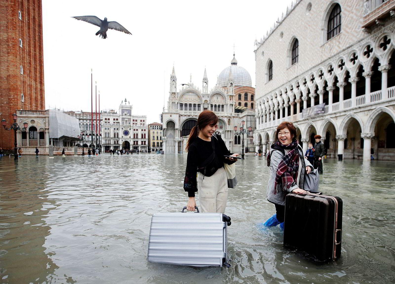 Turister flyter bagasjen sin over en oversvømmet Markusplass i Venezia.
