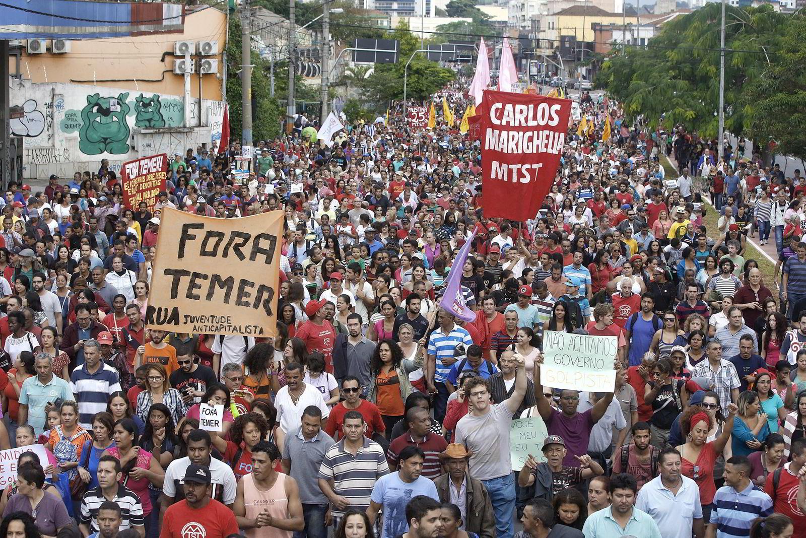 Skilt og bannere med teksten «Temer ut!» under demonstrasjoner mot Michel Temer, bare uker etter at han ble utnevtn til Brasils president. Foto: AP Photo/Andre Penner/NTB Scanpix