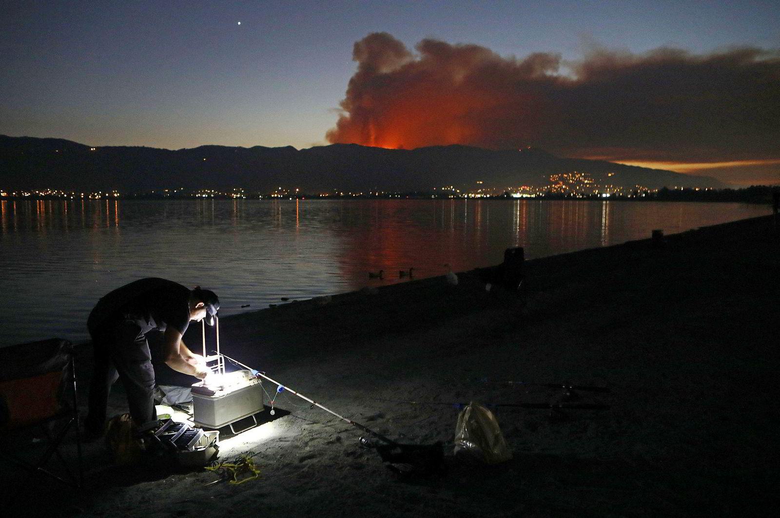 En mann forbereder seg til å fiske mens røyken fra skogbrannene stiger i bakgrunnen. Så langt antar man at flammene i California har brent av rundt 600.000 dekar.