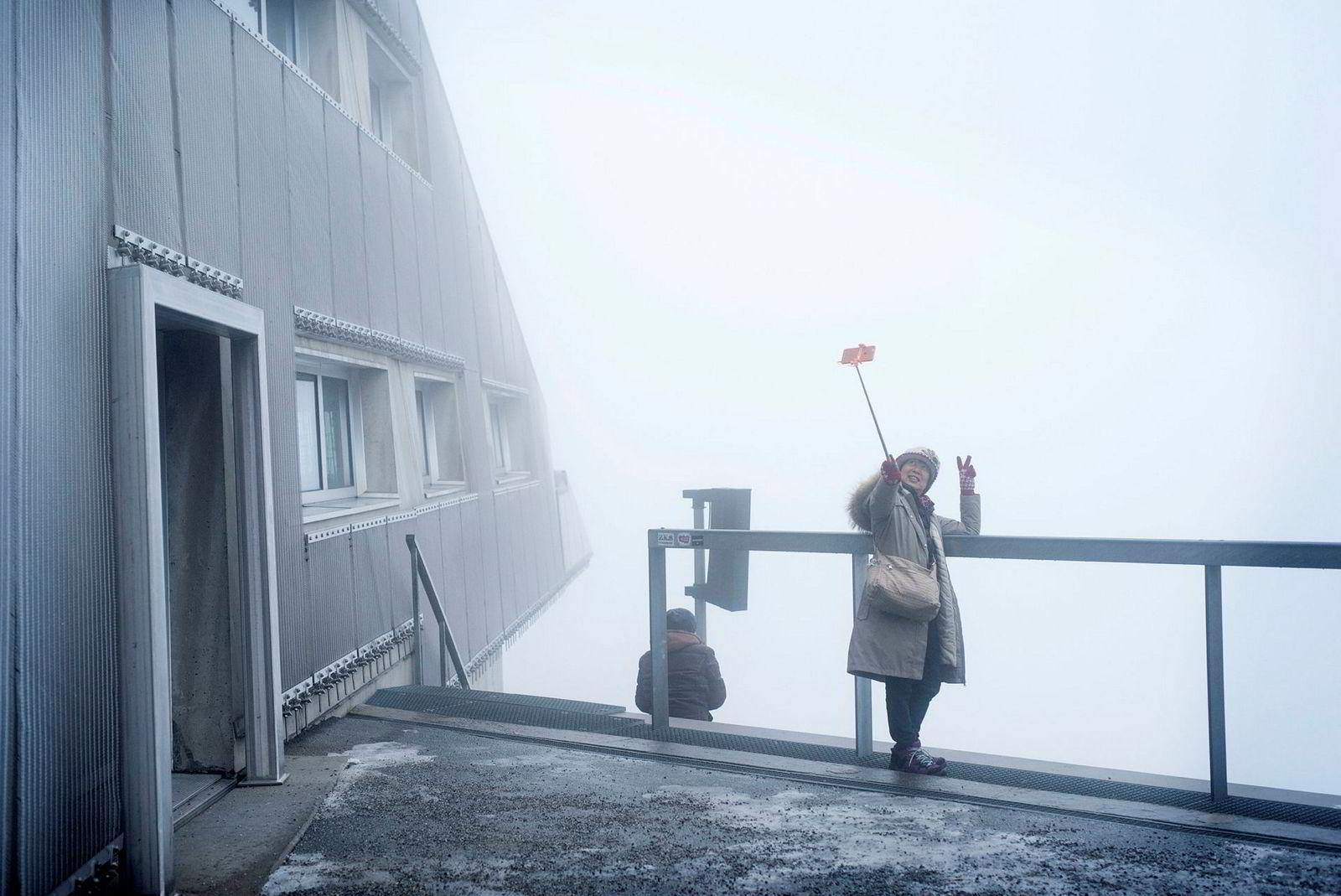 Regina Wu jobber hardt for den perfekte selfien i tåkehavet på toppen av Holmenkollbakken.