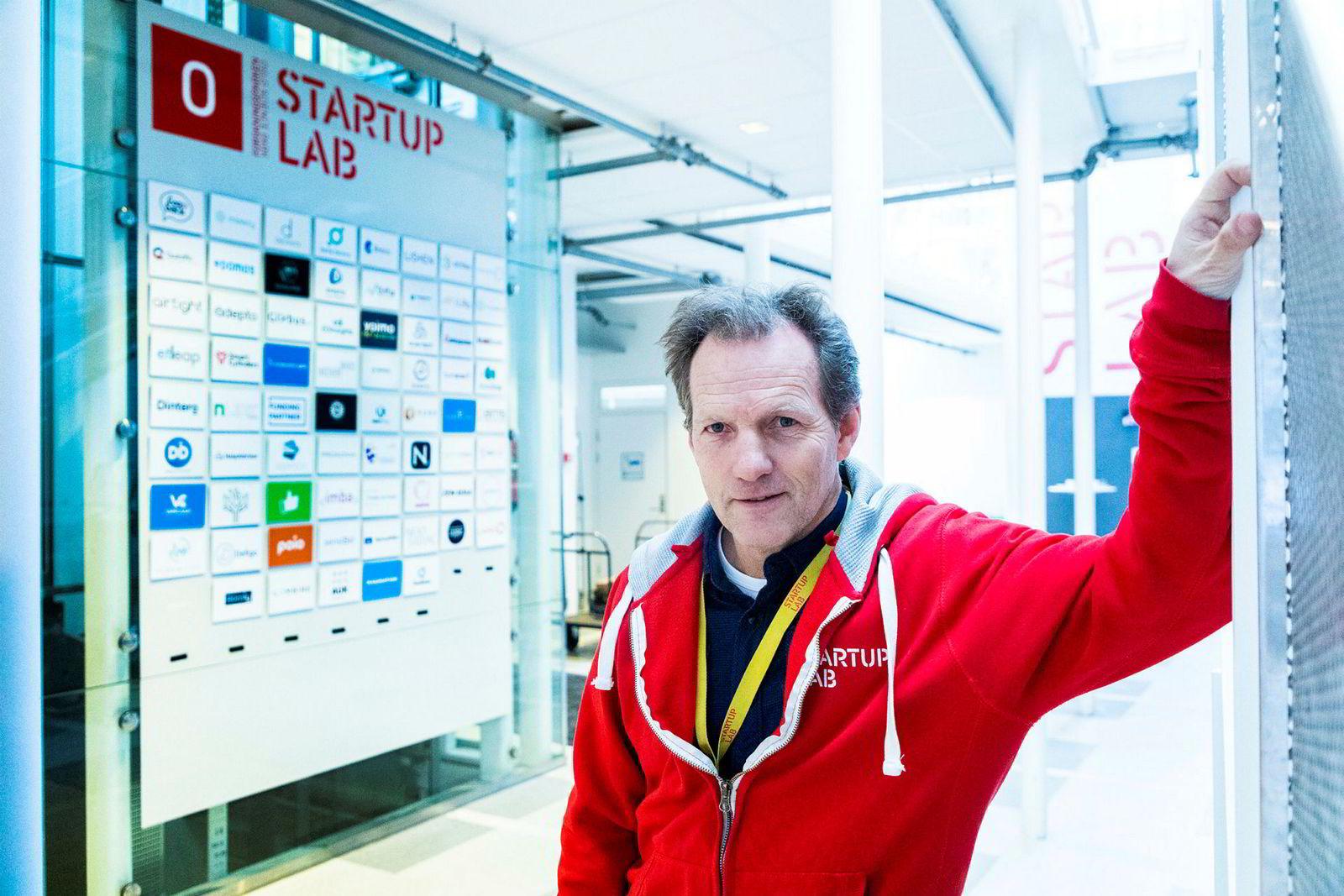 Rolf Assev, partner i StartupLab, ved tavlen med skiltene til selskapene som er en del av gründerfellesskapet.
