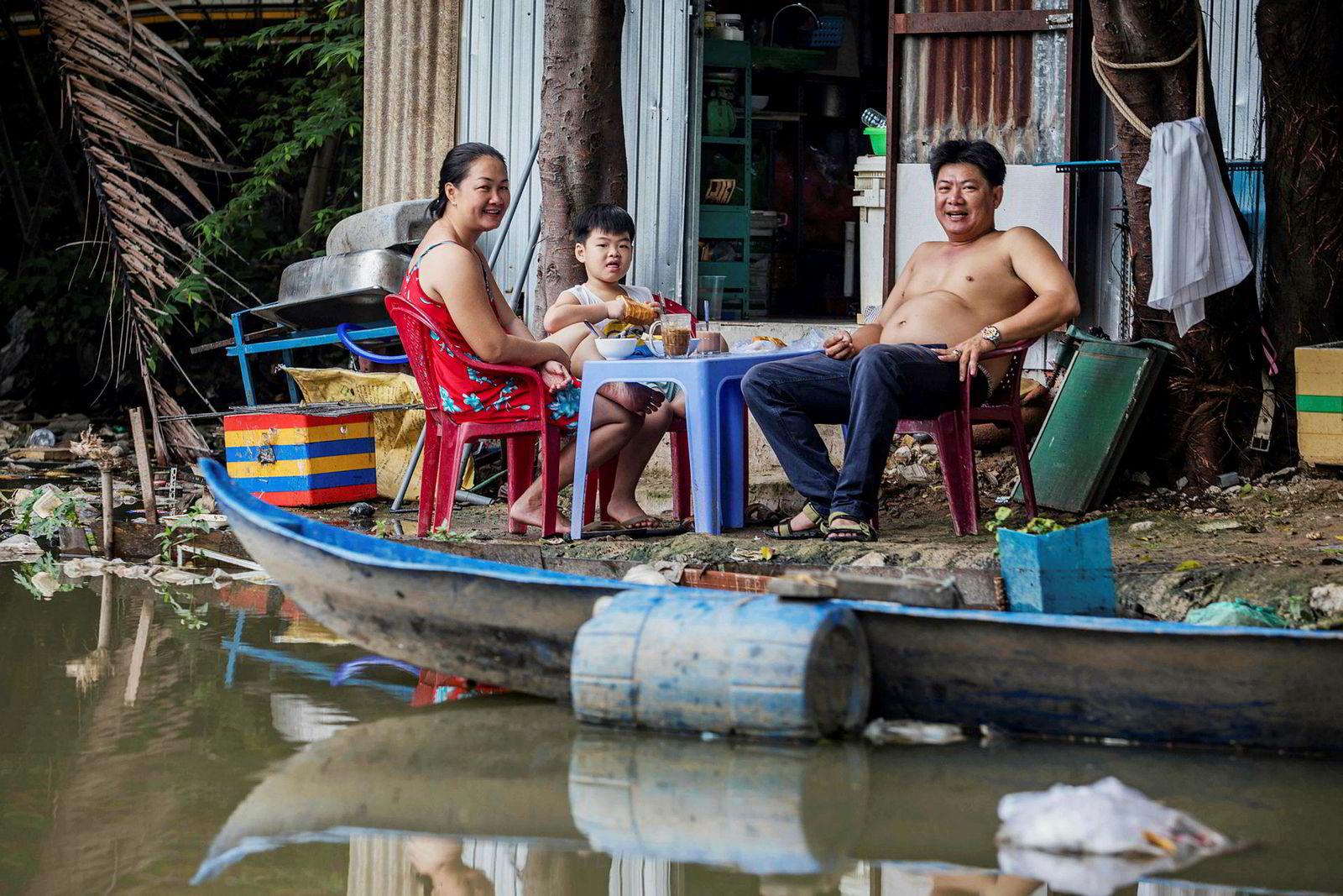 En familie sitter utenfor huset sitt på elvebredden ved Xuyen Tam-kanalen.