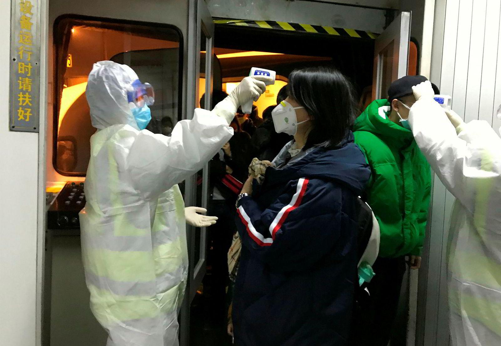 Reisende fra Wuhan sjekkes ved ankomst til Beijing. Fra torsdag morgen isoleres millionbyen. Dette skjer i håp om å begrense spredning av det dødelige coronaviruset.