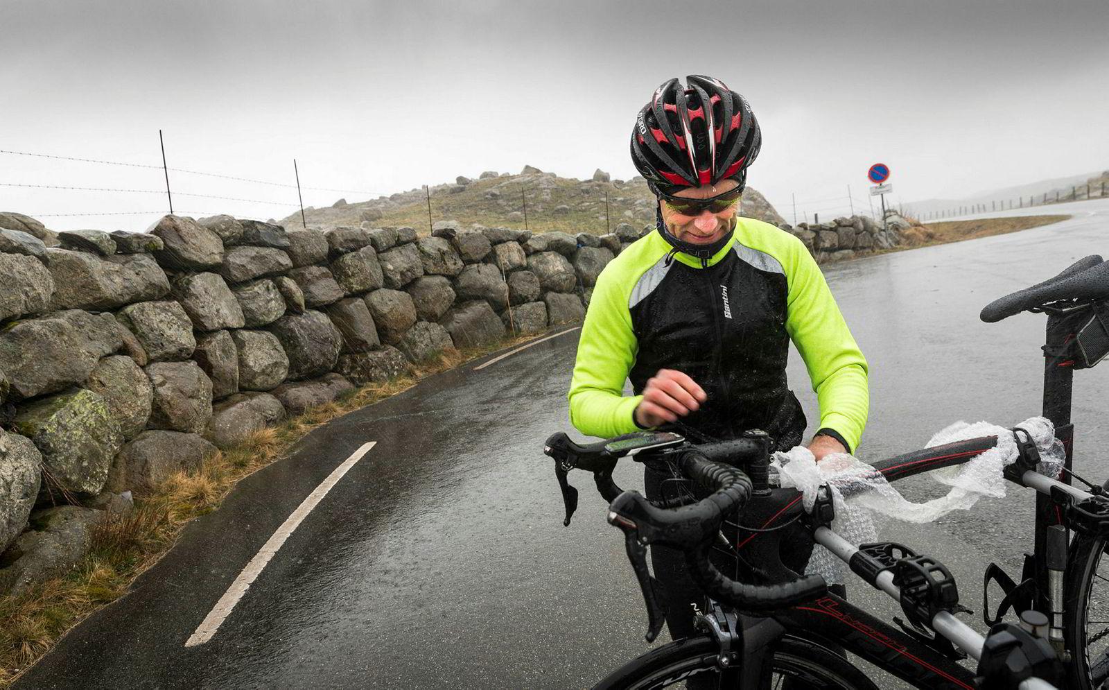 Johnny Stausholm kjemper mot øsende regnvær i det han fester sykkelen på stativet bakpå bilen. Det er ikke dagen for en lang økt.