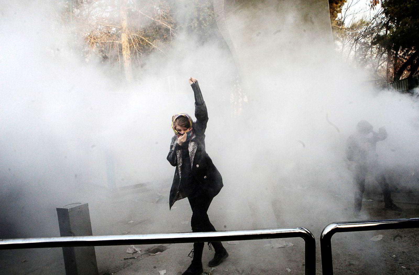 En iransk kvinne hever armen i røyken fra tåregassen ved universitetet i Teheran under demonstrasjonene sist lørdag, som var den tredje dagen på rad med protester.