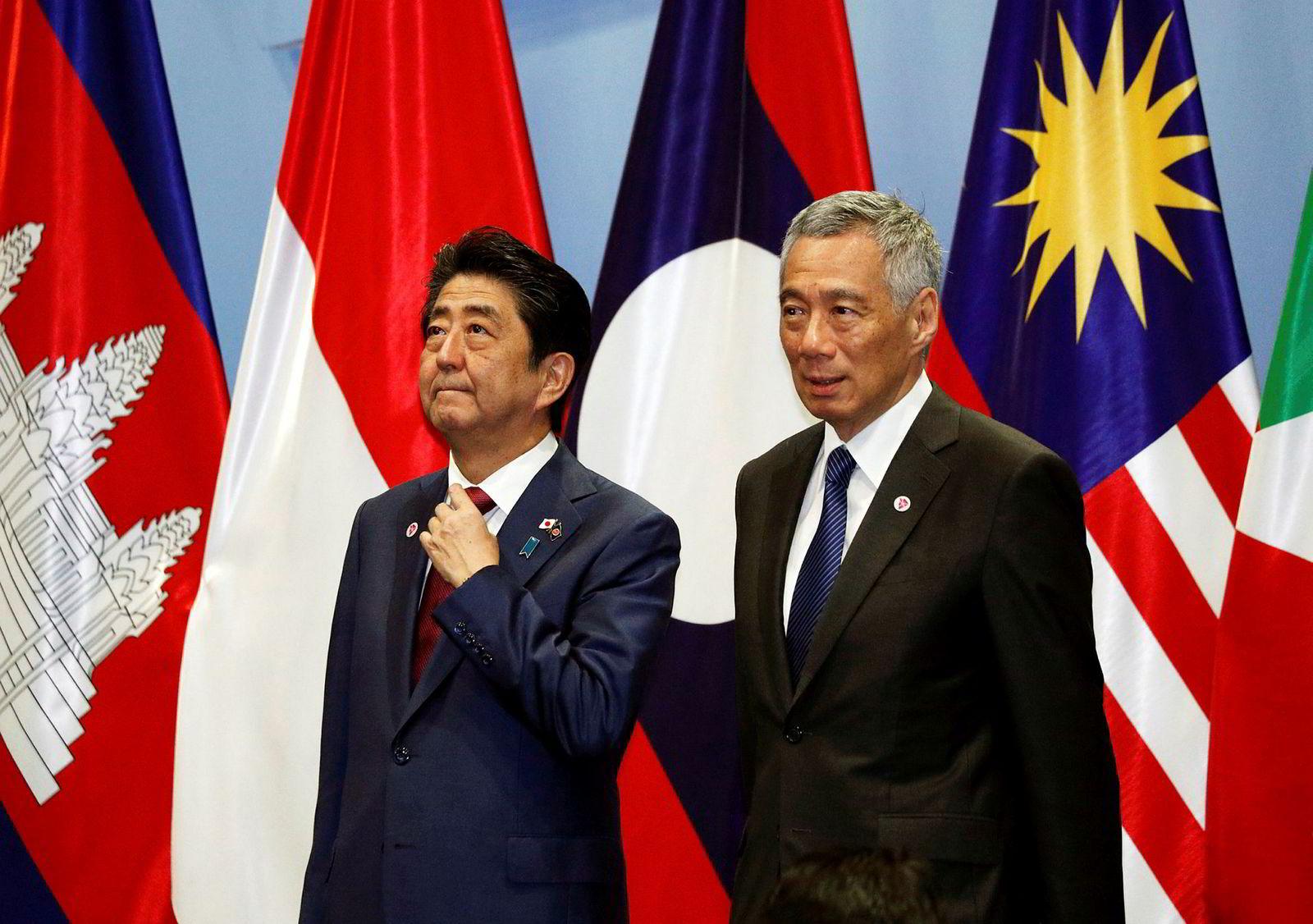 Japans statsminister Shinzo Abe (til venstre) sammen med sin kollega fra Singapore, Lee Hsien Loong, under gruppefotograferingen på onsdagens toppmøte.