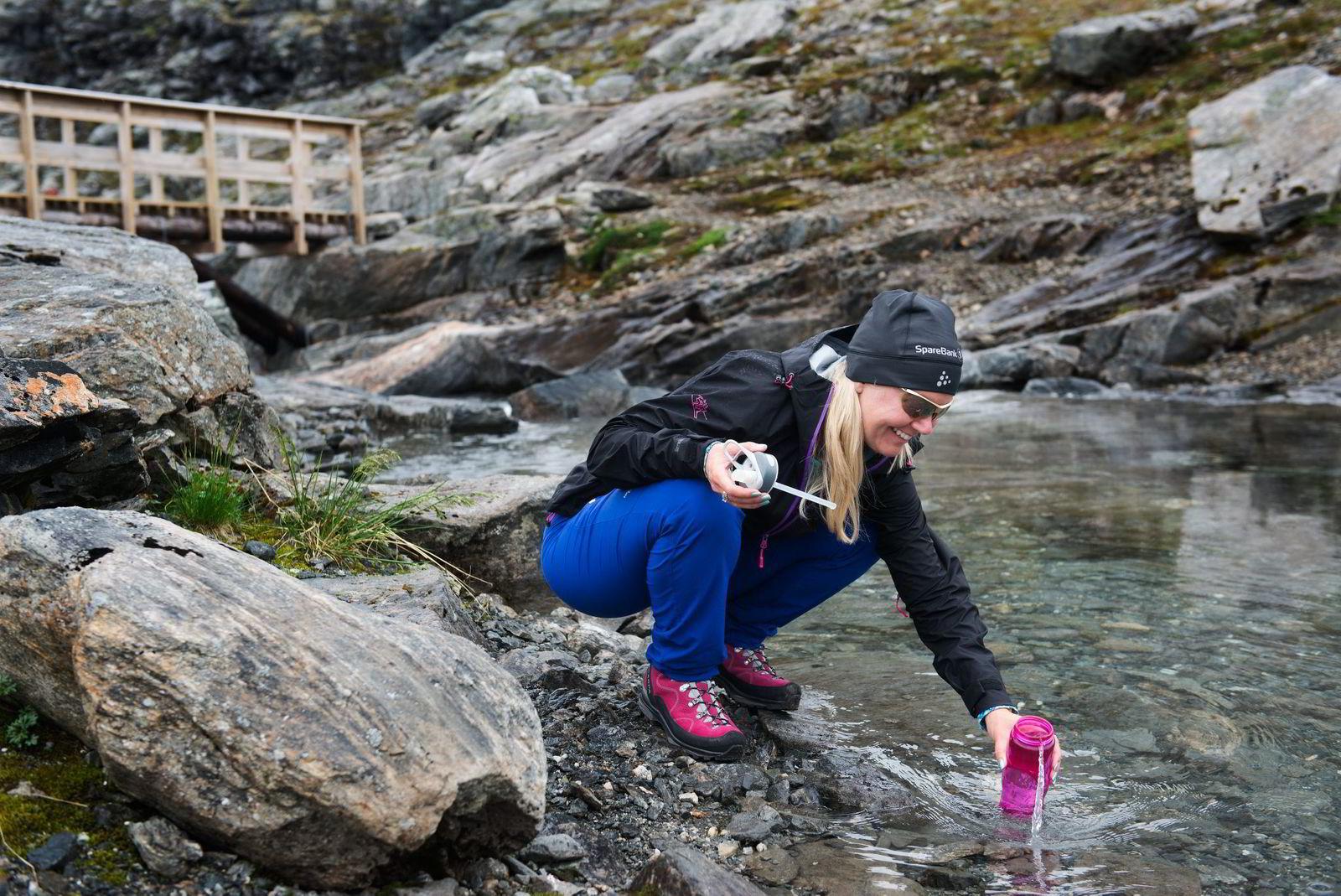 Mona Andersson fyller opp vannflasken med kaldt fjellvann på vei opp til fjelltoppen Bispen.