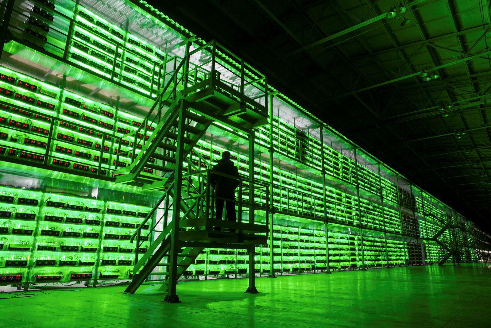 En væpnet vakt bruker en novemberdag til å passe på et stort antall datamaskiner som utvinner kryptovaluta i Bratsk i Russland.