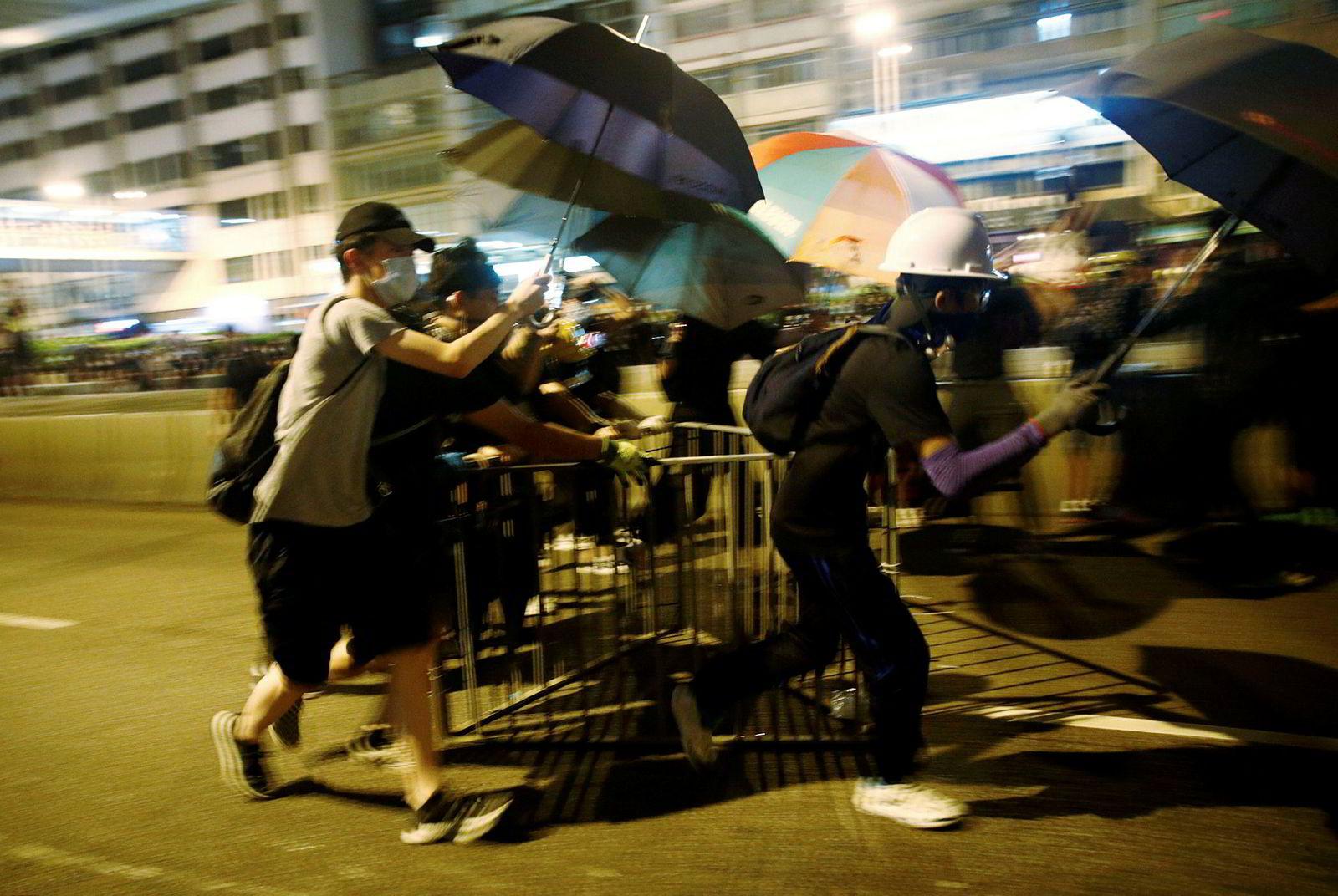 Demonstrantene løper for å lage barrikader mot politiet.