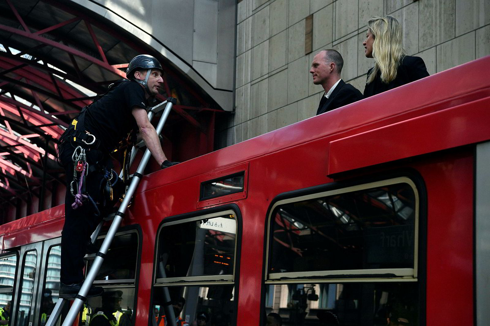 Politiet snakker med aktivister som har klatret opp på et tog og limt seg selv fast til en togvogn på Canary Wharf stasjon øst i London. Stuntet er en del av klimaprotestene til Extinction Rebellion.