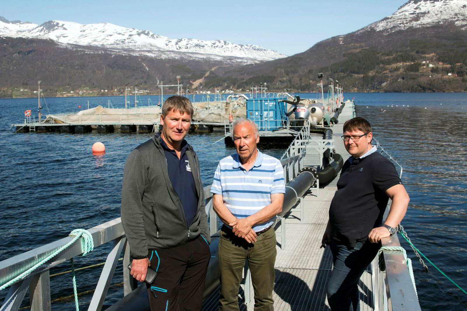 Fra venstre daglig leder Tore Lundberg i Gratanglaks, daglig leder Odd Bakkeli i Salaks og driftsleder Lars Berg i Kleiva Fiskefarm. Her foran tomme ventemerder ved lakseslakteriet i Gratangsfjorden.