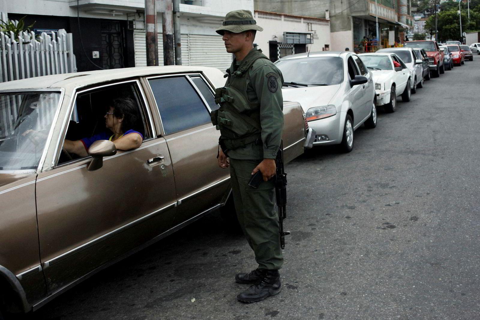 Venezuela har verdens største påviste oljereserver, mens det er bensinmangel i landet. Her holder soldater orden på køen ved en bensinstasjon i byen San Cristobal.