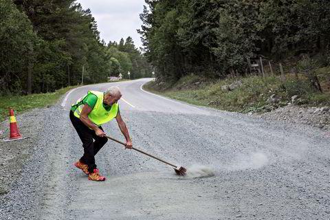 En frivillig koster febrilsk vekk en uventet hindring, før syklistene kommer med sine tynne dekk.
