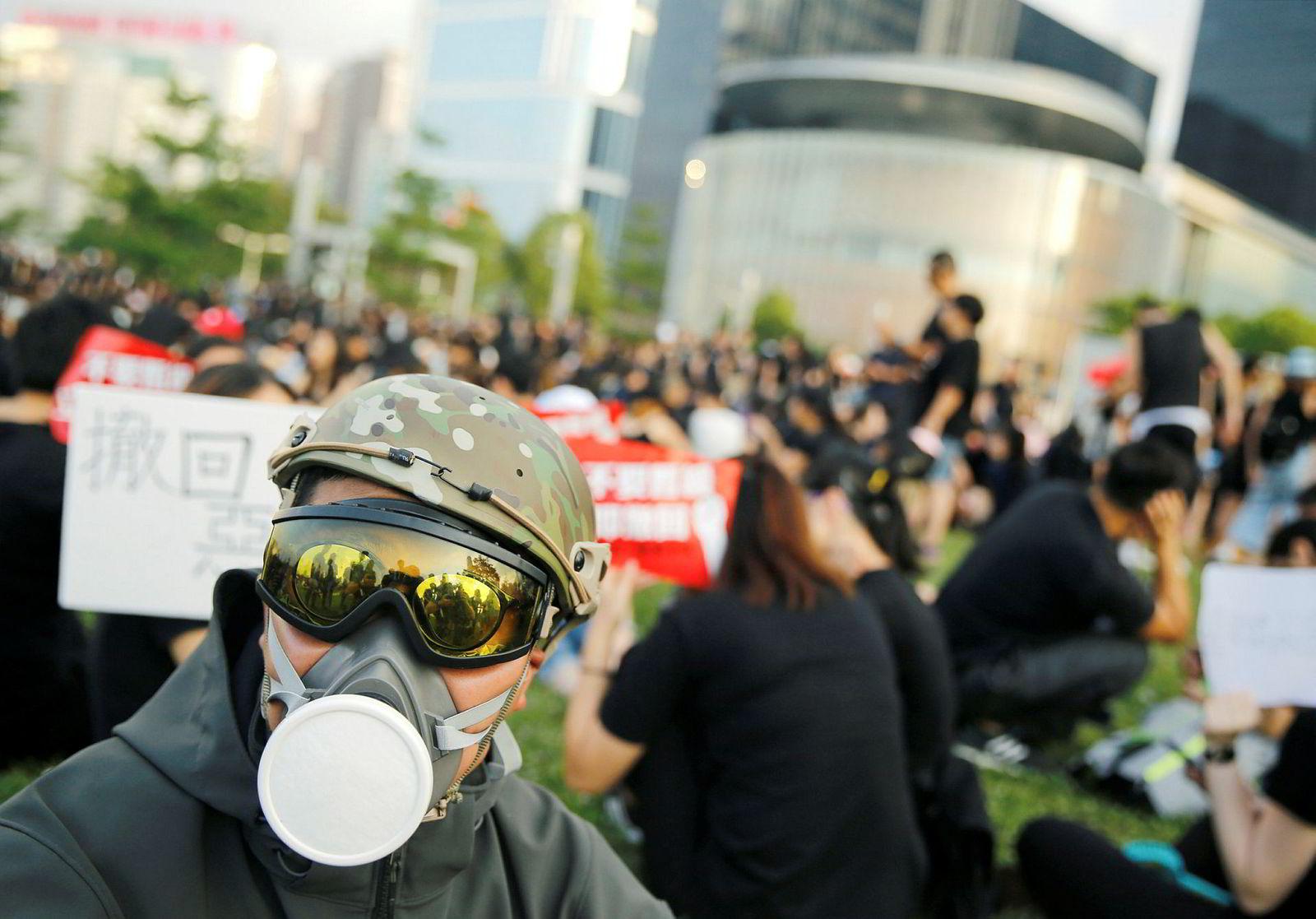 En demonstrant utenfor byens lovgivende forsamling, Legislative Council, var ikledd gassmaske. Bekledningen var antagelig på for å minne omverdenen på at politiet brukte pepperspray og tåregass mot demonstrantene sist onsdag.