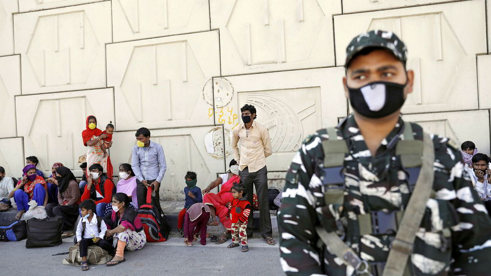Selv om myndighetene kunngjorde hjelpetiltak, stanset ikke det flukten. Lørdag ble det sendt busser og biler for å hjelpe tusener av mennesker som var samlet ved et veikryss utenfor New Delhi. Her venter arbeidere på de oppsatte bussene, i Ghaziabad utenfor New Delhi, lørdag.