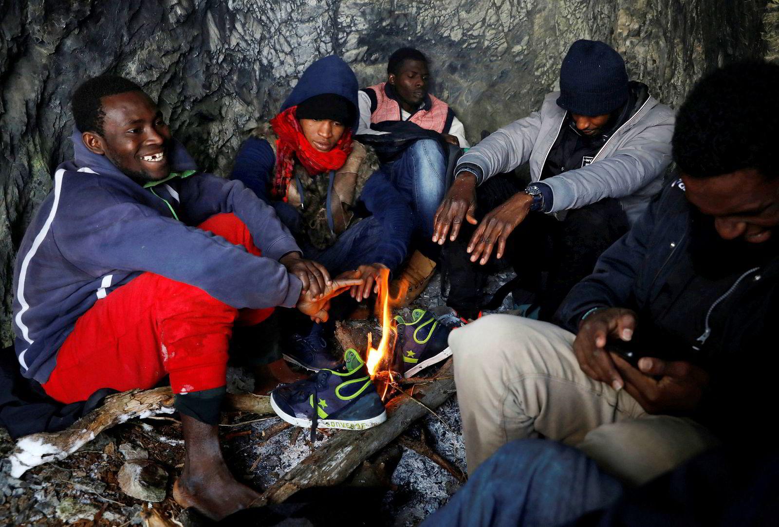 28-år gamle Kamarra (til venstre) fra Guinea og en gjeng innvandrere forsøker å få varmen i seg etter å ha krysset deler av Alpene fra Italia til den franske alpelandsbyen Nevache. Bildet er tatt i slutten av desember.