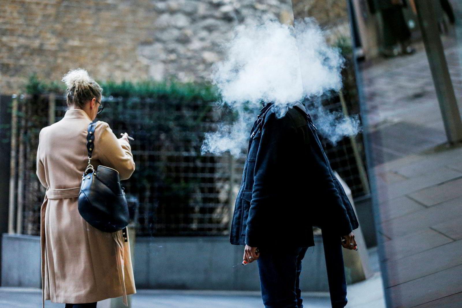 Et oktoberbilde fra en London-gate viser en tradisjonell sigarettrøyker som passerer en annen røyker innhyllet i dampen fra en e-sigarett.