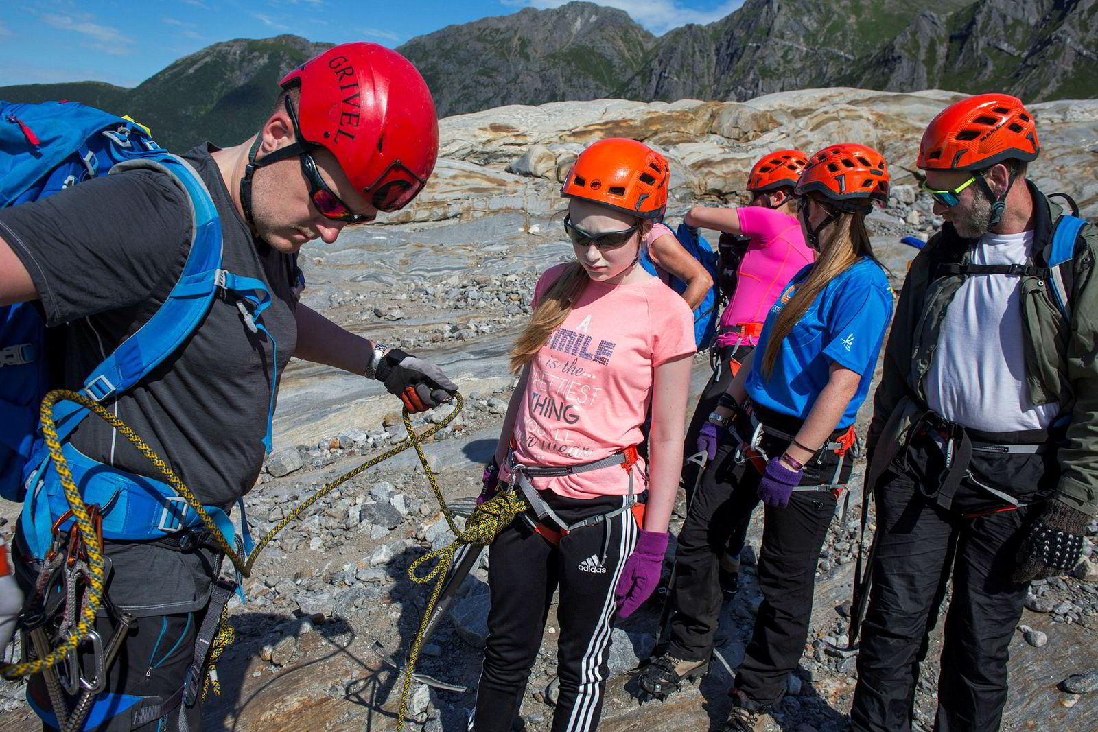 Øyvind Gjersvik fra Meløy Adventure hjelper Karen Norbotten inn i klatretauet før brevandringen starter. Bak står søstrene Birthe og Bolette mens far Rune Norbotten følger med fra siden.