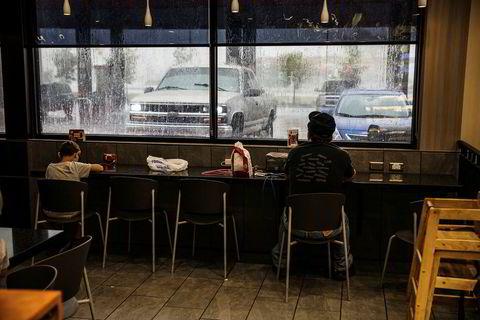 Folk søker tilflukt fra regnet på en åpen bensinstasjon.
