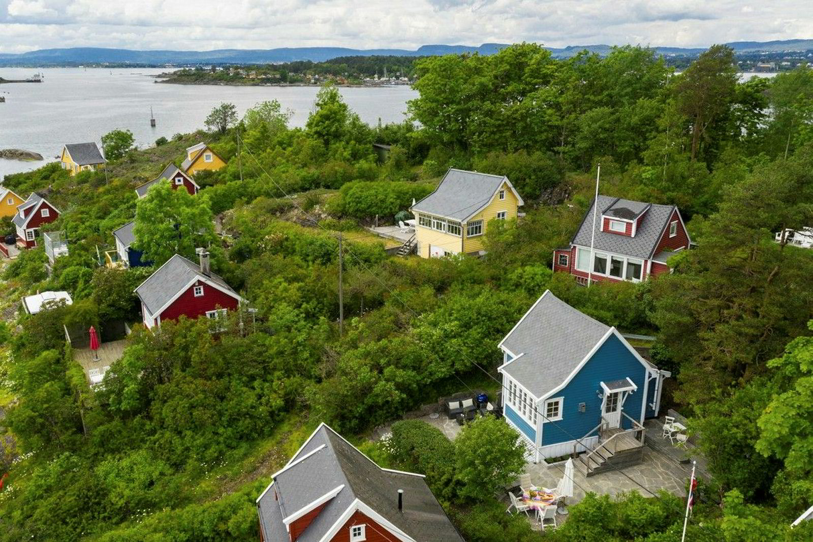 Bleikøya ligger sammen med Nakkholmen og Lindøya rett utenfor Oslo. Hytta som er solgt er den blå hytta til høyre i bildet.