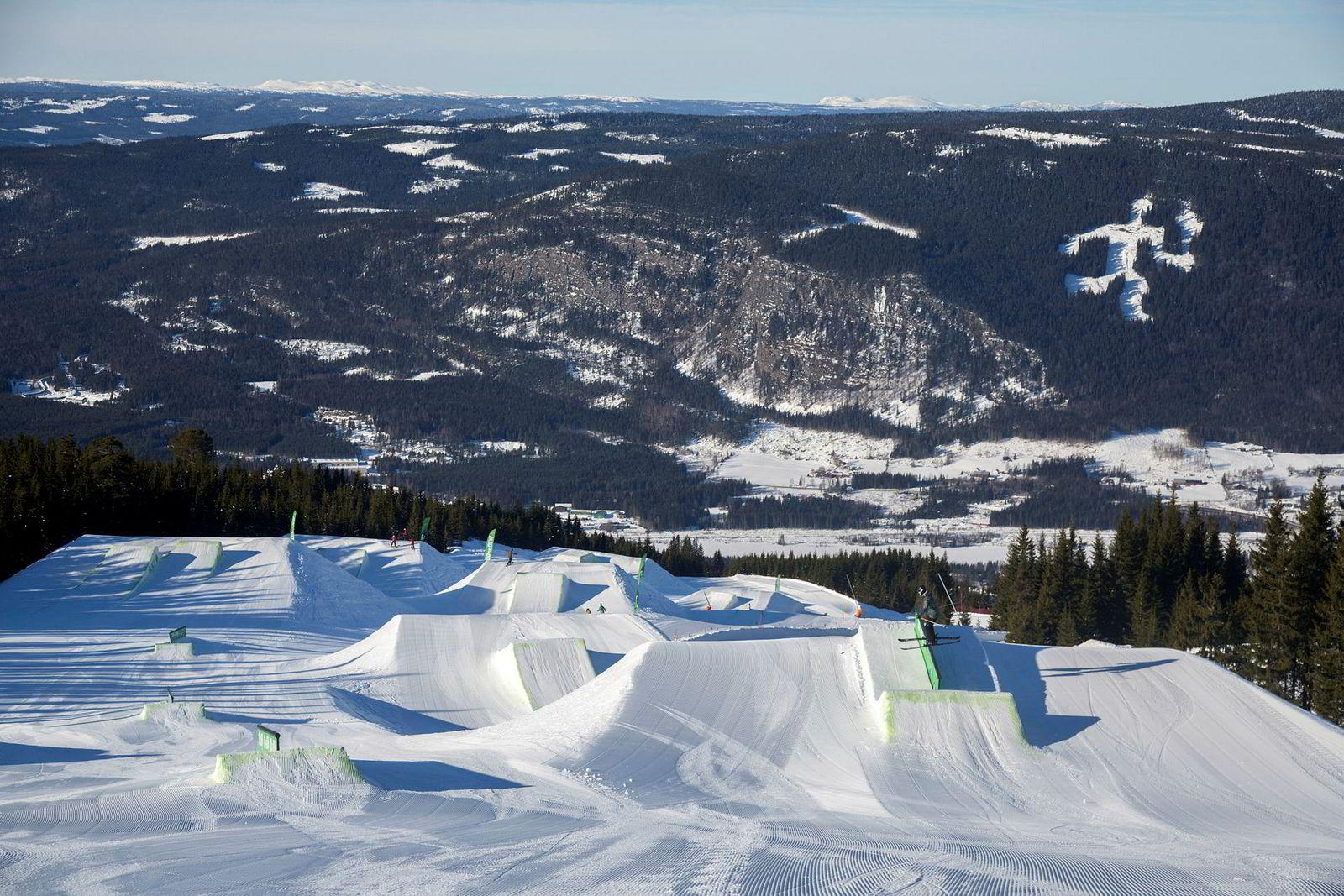 Med utsikt til fakkelmannen, setter juniorlandslagets Tora Johansen skiene på tvers og sklir over en rail i Hafjells mest krevende terrengpark.