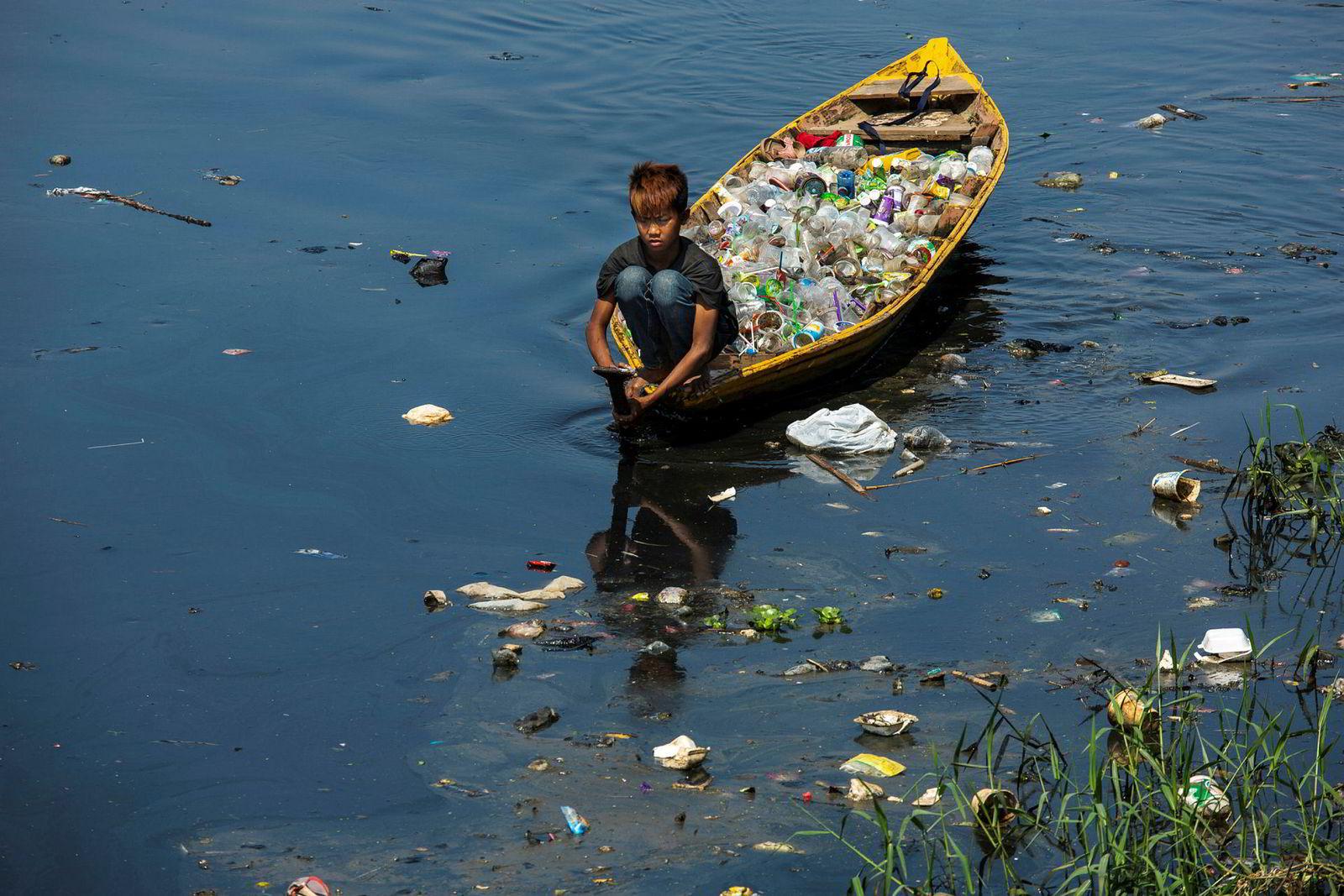 Fra en båt på Citarum-elven samler en gutt plastavfall som han senere kan selge. Elvevannet er farget svart av industriforurensning.
